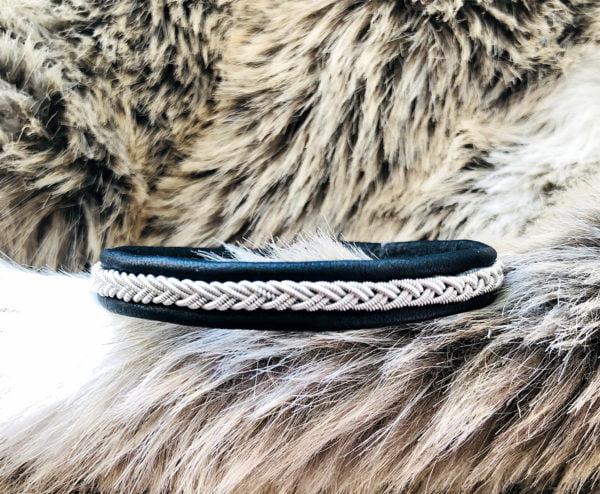 Armband av tenntråd och renskinn liggandes på en renpäls