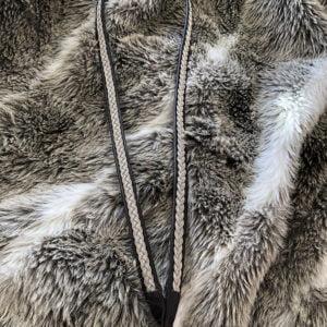 Nyckelband av tenntråd och renskinn liggandes på en renpäls
